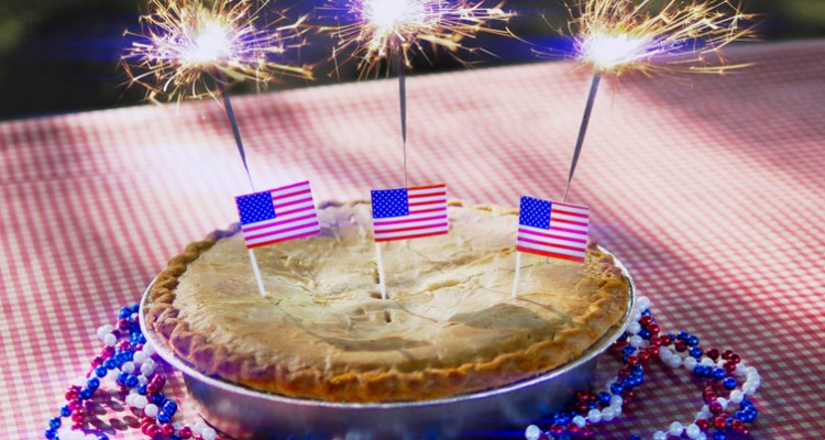 A Fourth of July apple pie with red, white, and blue beads, American flags, and sparklers on a picnic table with lens flare.